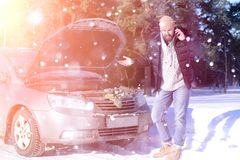 Man stands outdoor near broken car. A man stands in front of a broken car in the winter Stock Photo