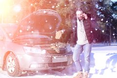 Man stands outdoor near broken car. A man stands in front of a broken car in the winter Stock Photos