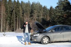 Man stands outdoor near broken car. A man stands in front of a broken car in the winter Stock Image