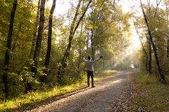 A man stands on a path strewn with yellow foliage, and stretches royalty free stock photography