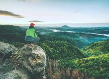 Man stands on the peak of rock. Hiker watching to autumn Sun at horizon . Beautiful moment royalty free stock photo