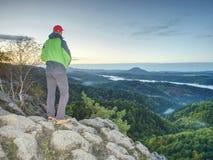 Man stands on the peak of rock. Hiker watching to autumn Sun at horizon . Beautiful moment. Man stands alone on the peak of rock. Hiker watching to autumn Sun at stock photography