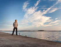 A man stands on the pier starring at the sea Stock Photo
