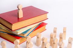 A man stands on a pile of books before the audience and makes a speech. A smart leader manages employees and leads them along. stock images