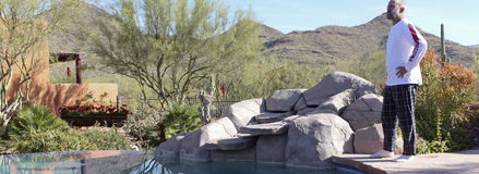 A Man Stands Poolside in Arizona`s Sonoran Desert. A Middle Aged Bearded Man Stands Poolside in the Sonoran Desert  of Arizona Royalty Free Stock Photography
