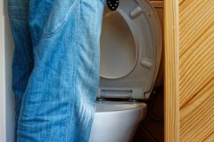 A man stands releiving himself in front of a white porcelein toilet. stock photos
