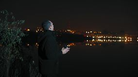 A Man Stands on the River Bank and Drinks Tea Late in the Evening stock video