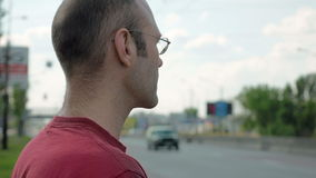 Man stands by roadside of city street traffic stock footage