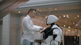A man stands with a robot bot and asks him questions and asks for help by clicking on the screen on the robot body. stock video footage