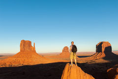 Man stands on a rock against the backdrop of Monument Valley Stock Images