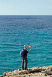 Man stands on a rock and looking at blue sea Royalty Free Stock Photos