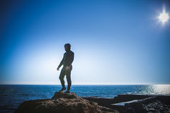 Man stands on a rock by the sea against the sky Stock Photography