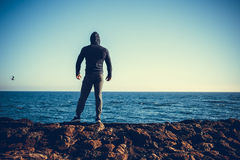 Man stands on a rock by the sea. Against the sky stock photo