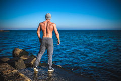 Man stands on a rock by the sea against the sky Stock Image