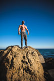 Man stands on a rock by the sea against the sky Stock Photo