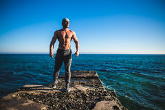 Man stands on a rock by the sea against the sky Royalty Free Stock Photo