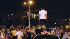 A man stands on the roof of the car at street party of night city among crowd. Russia, Novosibirsk, July 2, 2018: Victory of Russia in a football match. In the stock video