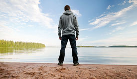 A man stands on the sand lake coast Royalty Free Stock Photo