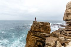 Man stands on a sea cliff, looking into the distance on a dark stormy sea. Young guy travel on the sea and stay on rocky shore under cloudy sky Stock Photos