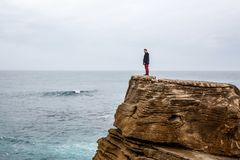 Man stands on a sea cliff, looking into the distance on a dark stormy sea. Young guy travel on the sea and stay on rocky shore under cloudy sky Stock Photography