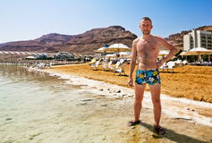 A man stands on the shore of the dead sea Stock Photo
