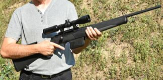Man stands with a shotgun. Outdoor stock image