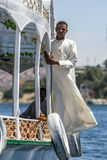 A man stands on the side of a tourist boat on the River Nile in Egypt. A man stands on the side of a tourist boat as it navigates its way along the River Nile Stock Photos