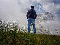 A man stands on a slope and admires the tops of mountains in the clouds stock photos
