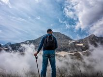 A man stands on a slope and admires the tops of mountains in the clouds stock image