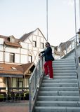 A man stands on the stairs. A man in black glasses and red trousers stands on the stairs and looks into the distance stock image