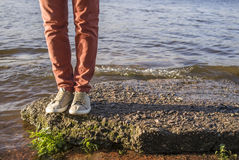 Man stands on the stone by the river with small waves Stock Photography