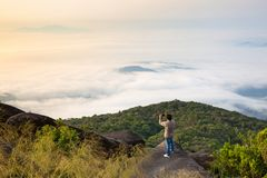 A Man on the edge over the sea of cloud. A man stands on the summit of the mountain in the lower left corner of the image with sea of fog, morning sky with Stock Images