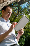 Man stands with tablet near the tree Royalty Free Stock Photography
