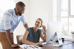 Man stands talking to woman smiling at her desk in an office Stock Images