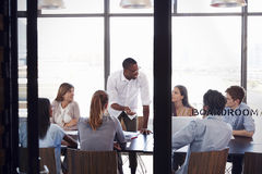 Man stands to address colleagues at a meeting in a boardroom Royalty Free Stock Images