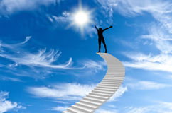 Man stands on top. Of Stairs and extends to the sun Stock Photos