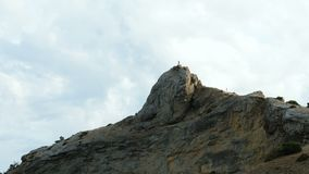 A man stands on the top of a cliff. A man stands on top of a cliff and shoots nature on a mobile phone stock video footage