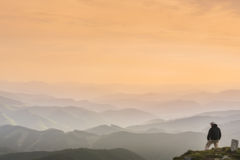 A man stands on top of a mountain and looks into the distanceon Royalty Free Stock Photography