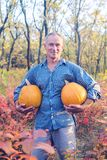 Man stands with two huge pumpkins among the colorful autumn leav. Proud man stands with two huge pumpkins in his hands in the forest, among the colorful autumn Royalty Free Stock Photography