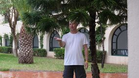 Man stands under tree branches during rain summer day and lookig on his palm at rain drops.  stock footage