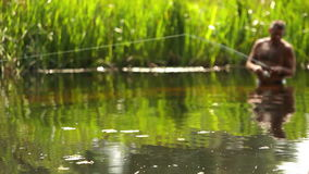A man stands waist-deep in the water and throws a line to catch fish stock footage
