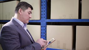 Man stands in the warehouse and keeps the tablet. stock video