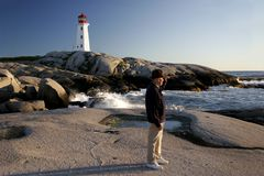 Man views the sea at Peggys Cove. A man stands by the water looking out, watching and waiting for something Stock Photos