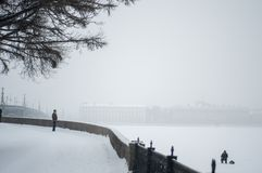 City covered with snow. Man stand on waterfrontWinter travel in Russia. Saint Petersburg stock photo