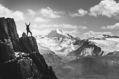 Man stands in winner pose on the cliff. Greyscale. Man with rised hands stands in winner pose on the cliff on background of mountains Stock Photography