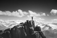 Man stands in winner pose on the top of mountain stock photo