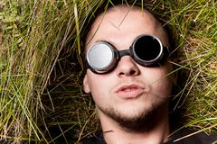 Man stare to you through glasses, think about it. Bald man in grass stare to all of you through round glasses, think about it Stock Images