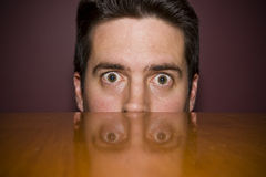 Man stares fearfully over a table Stock Photo