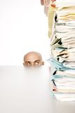 Man stares at files. A bald man stares up at a large stack of file folders. Only the eyes and top of his head are visible. White background Royalty Free Stock Photo