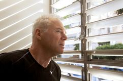 Man stares out the window through the blinds royalty free stock images